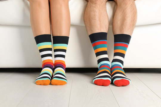 Young couple in matching socks on couch indoors, closeup