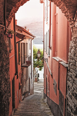 Wall Mural - Village Carate Urio on Como lake. Spectacular sunrise city scene on narrow street in old medieval town. Typical old Italian town scenery. Vintage style photo.