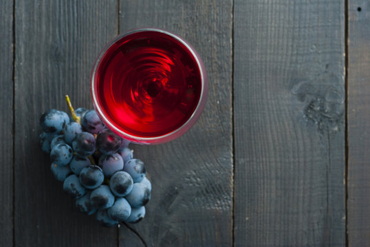 glass of red wine and grapes on black wood table background