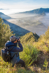A man traveler with shooting photo amazing nature near  of  Mount BROMO at indonesia