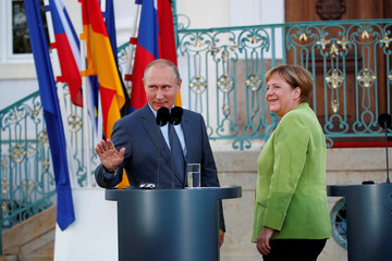 Putin gestures next to Merkel at Meseberg Palace in Gransee