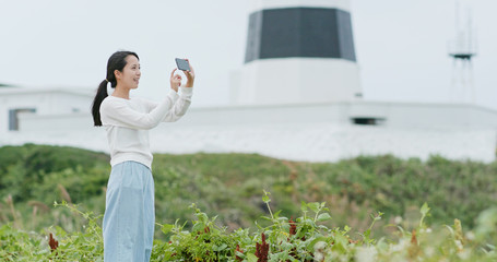 Asian Woman use of cellphone to take photo at outdoor