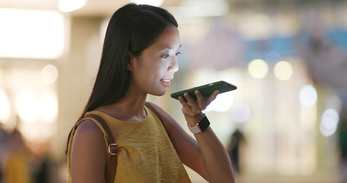 Woman sending audio message on cellphone at outdoor in the evening