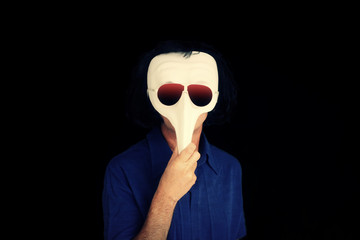 A bizarre weird man hiding behind a classical theatrical white mask and graded sunglasses.
