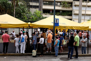 People wait in a queue to buy food in a street market in Caracas