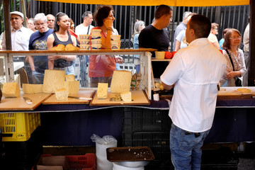 People wait in a queue to buy cheese in a street market in Caracas