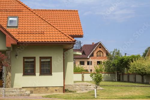 New Nice One Story Cottage With Shingle Roof Balcony Plastic Attic Windows Paved Yard Green Lawn And Decorative Blooming Trees On Bright Blue Sky