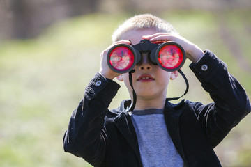 Portrait of little cute handsome cute blond boy watching intently something through binoculars in distance on blurred background. Children innocence, dreams, fantasies and imaginations concept.