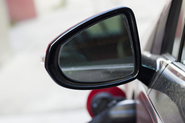 Close-up detail part of dirty back side view car mirror with blurred reflection on white copy space background. Transportation, safety, modern technology and vehicle design concept.