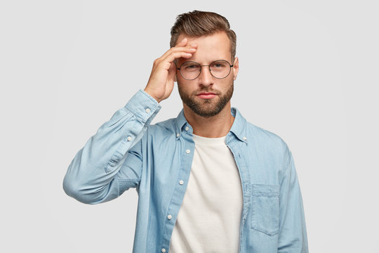 Horizontal shot of serious unshaven male has pensive expression, keeps hand on forehead, tries to gather with thoughts, dressed in blue shirt, being intelligent, isolated over white background