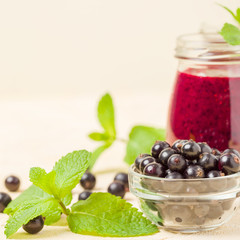 Currant smoothie decorated with fresh green mint leaves and raw ripe berries on yellow pastel background.