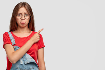 Indoor shot of displeased young lovely female has offended expression, points at upper right corner, doesnt like something, wears casual red t shirt and denim overalls, isolated over white background