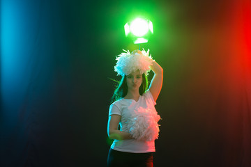 Dancing, cheerleading and people concept - young girl in darkness under colourful light with pompoms on her head