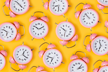 Pink alarm clock on yellow background.