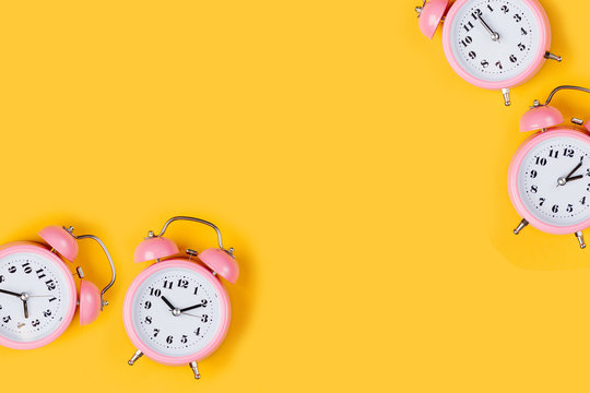 Pink alarm clock on yellow background.