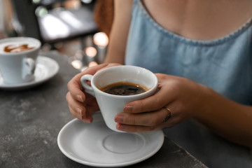 Woman with cup of fresh aromatic coffee at table, closeup