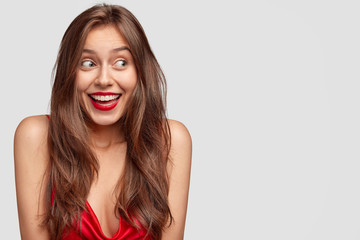 Attractive young female with long dark straight hair, has happy expression, red lips, dressed casually, stands against white background with copy space for your advertisement or promotional text