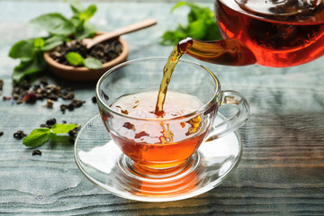 Poster de jardin The Pouring black tea into glass cup on wooden table