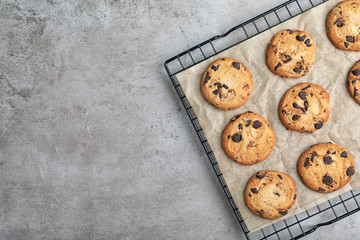 Cooling rack with chocolate cookies and space for text on gray background, top view