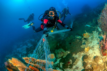 SCUBA divers attempting to remove a huge ghost fishing net tangled over a large area of a tropical coral reef