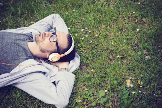 Relaxed man enjoying in music while lying on grass. Man taking day off and relaxing in nature with headphones.