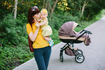 Young mother walking with baby carriage in the park, evening sun shine