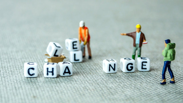 Removing white cubes with letters l and e of the word challenge creating new word change on grey background with miniature figurines