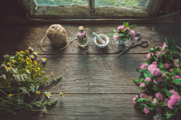 Pink clover, daisies and hypericum flowers, mortar, clover tincture or infusion, scissors and jute on old wooden table.