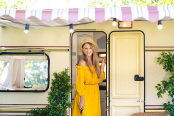 Cheerful pretty girl in yellow bohoo festival dress at the caravan camping