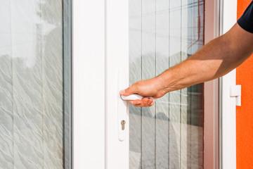 hand opens pvc balcony door