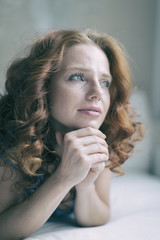 young redhead woman thinks about