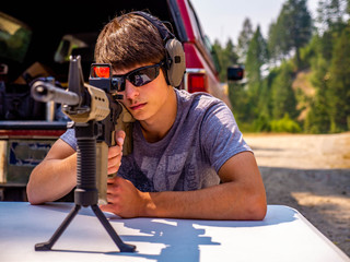 A young man concentrates as he fires his rifle at a paper target down range.
