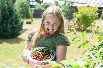 Happy girl picking cherry