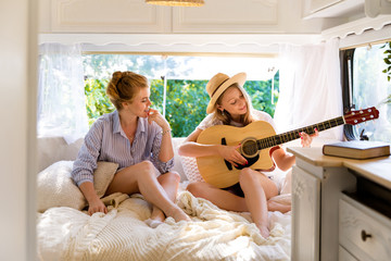 Beautiful girls in a camper van, with a guitar and hat. Road trip with best friends. Adventure, freedom, youth
