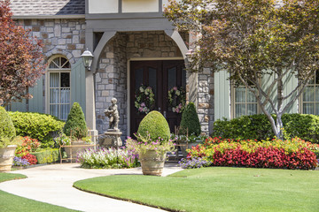 Entrance to upscale rock house with beautiful landscaping and a statue and wreaths and benches beside front porch