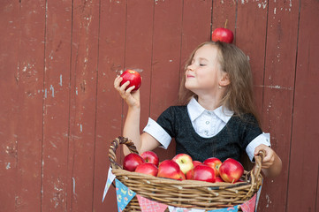 Cute little girl with a basket of red apples