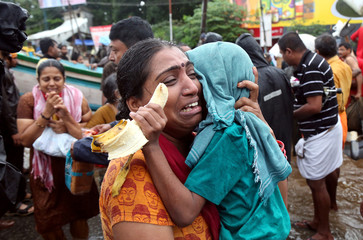 A woman cries as she holds her son after they were evacuated from a flooded area in Aluva