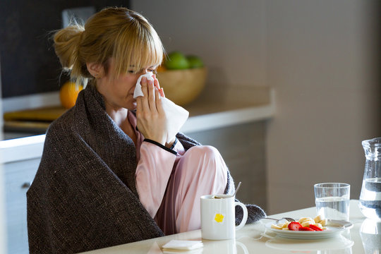 Illness young woman sneezing in a tissue at home.