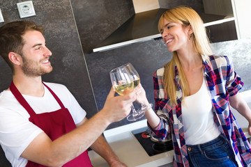 Happy young couple cooking together and toasting with glasses of white wine in the kitchen at home.