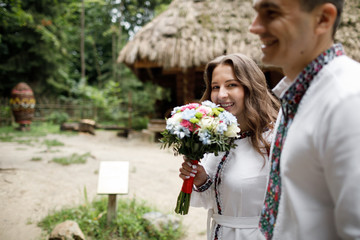 Beautiful bride and groom in the ukrainian style are standing w
