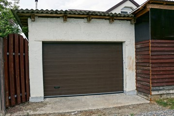 garage facade with a closed brown door and part of the fence in the street