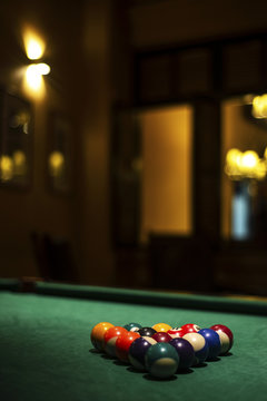 billiards balls on pool table in cozy dark bar interior