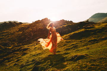 Beautiful woman run in fashion dress on nature