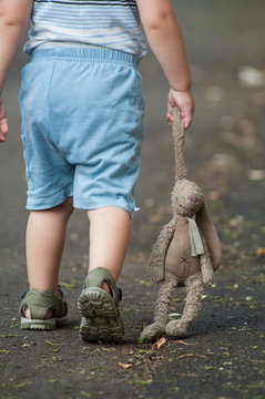 closeup of child walking in the street with plush rabbit in hand  dragging on the floor