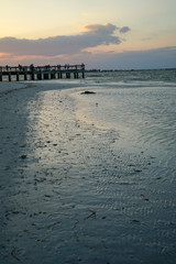 Colorful Sunset and waves on beach at Sanibel Pier on Sanibel Island in Florida