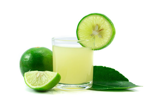 Glass of lime juice with lime half isolated on white background
