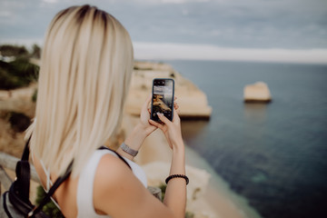 Young beauty woman take photo on the phone of beautiful ocean landscape with water and cliff in Portugal. Travel concept.
