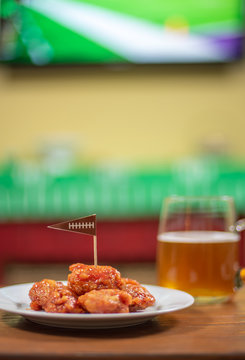 plate of boneless hot wings and beer with sports on TV in background