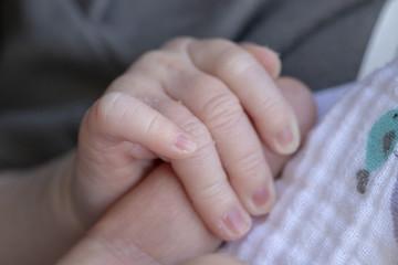 A Newborn Babies Hand around a Mans Finger
