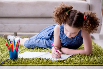 Young little girl drawing on paper with pencils